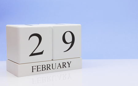February 29st. Day 29 of month, daily calendar on white table with reflection, with light blue background. Winter time, empty space for text