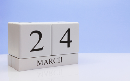 March 24st. Day 24 of month, daily calendar on white table with reflection, with light blue background. Spring time, empty space for text