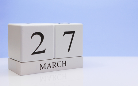 March 27st. Day 27 of month, daily calendar on white table with reflection, with light blue background. Spring time, empty space for text