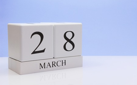 March 28st. Day 28 of month, daily calendar on white table with reflection, with light blue background. Spring time, empty space for text