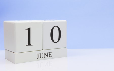 June 10st. Day 10 of month, daily calendar on white table with reflection, with light blue background. Summer time, empty space for text