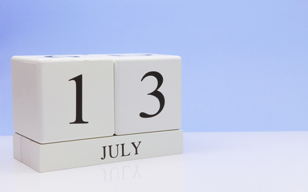 July 13st. Day 13 of month, daily calendar on white table with reflection, with light blue background. Summer time, empty space for text