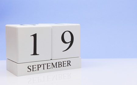 September 19st. Day 19 of month, daily calendar on white table with reflection, with light blue background. Autumn time, empty space for text