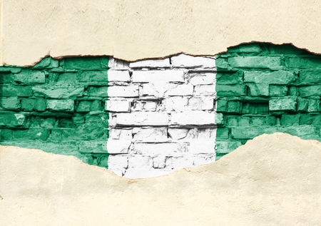 National flag of Nigeria on a brick background. Brick wall with partially destroyed plaster, background or texture.