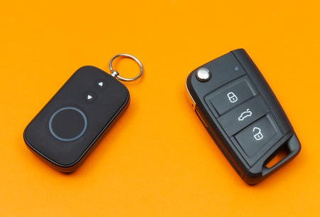 Car key with remote alarm control on the orange background Stock Photo