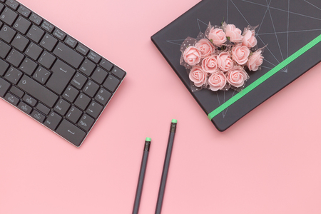 Top view, notebook with flowers and pencil with keyboard on pink background. Flat lay style Archivio Fotografico
