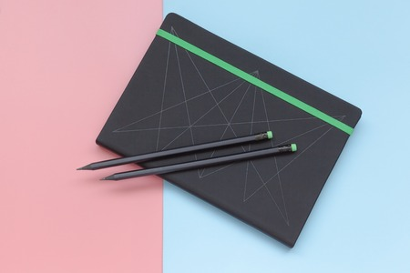 Top view, notebook and pencil on pink and blue background. Flat lay style