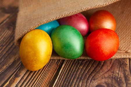 Colored Easter eggs on a wooden background in burlap
