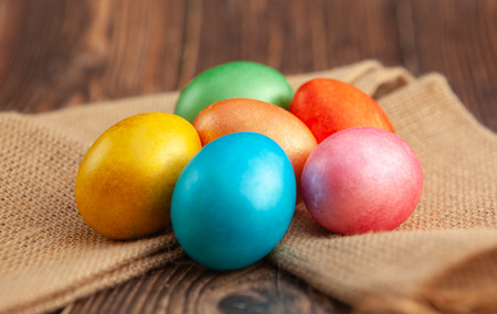 Colored Easter eggs on a wooden background on burlap