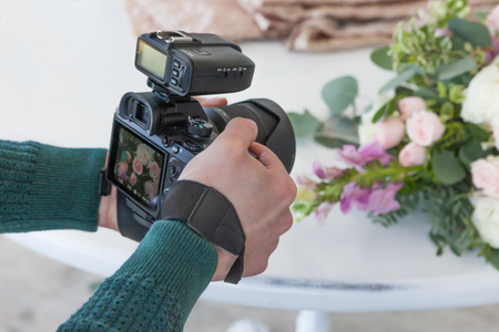 A young man makes a photo of a wedding bouquet, a picture on the camera screen. Stock Photo