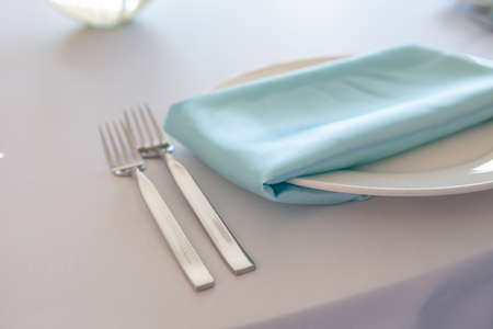 White plate with a turquoise napkin, metal fork and knife, table setting wedding