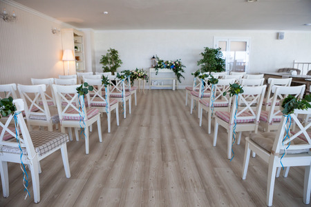 View of a wedding ceremony scene in a room with several rows of white chairs and compositions from different flowers