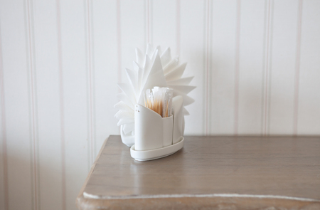 White napkins in holders on wooden table