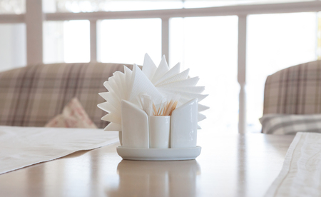 White napkins in holders on wooden table, close-up