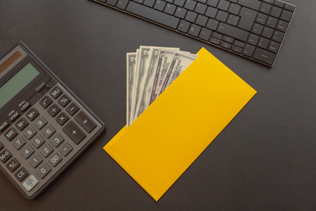 A yellow envelope with money on a dark leather desk, next to a calculator and keyboard. Business idea and high income creation concept