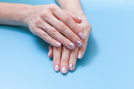 Beautiful female hands and a fashionable manicure on a blue background