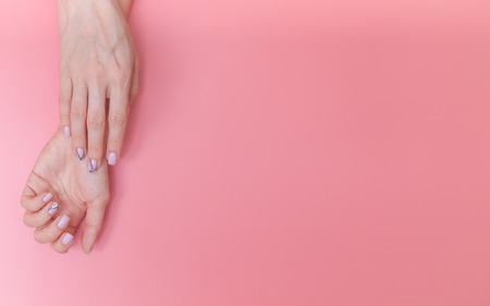 Beautiful, gentle female hands on a pink background with space for text.