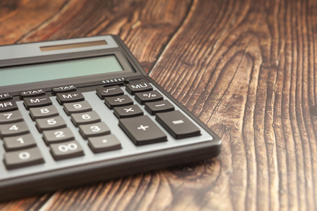 Modern calculator on a wooden table, business concept, close-up