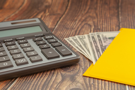 Modern calculator on a wooden table with a yellow envelope and money on a blurred background, business concept, close-up