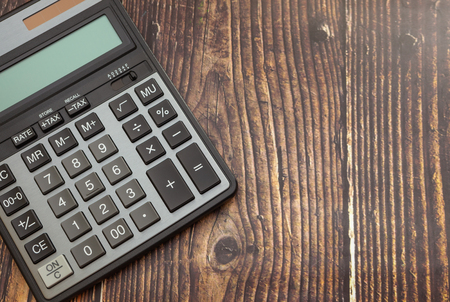 Calculator on wooden background, concept of business and saving finances