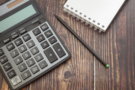 Calculator on wooden background with notepad and pencil, concept of business and saving finances
