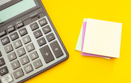 Modern calculator with stickers for notes on a yellow background, top view Banco de Imagens