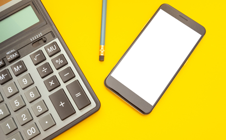 Modern calculator and phone with space for text on a yellow background, top view Banco de Imagens