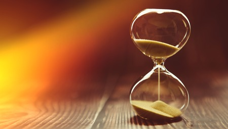The sunbeam penetrates the hourglass, symbolizing the beginning of time or the final time. Clock on a wooden background.
