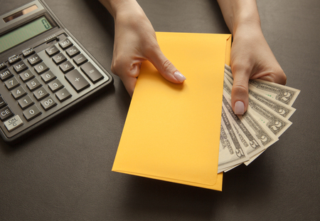 Concept of receiving salary in an envelope. Yellow envelope with money on a dark table.