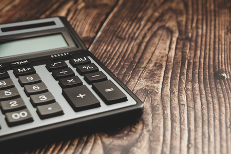 Modern calculator on a wooden table, business concept