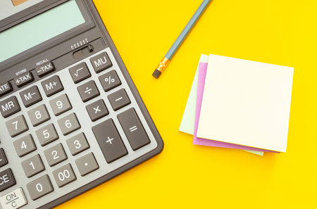Modern calculator and pencil with stickers for notes on a yellow background, top view Banco de Imagens