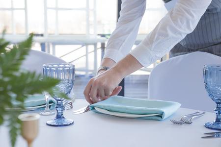 Restaurant waiter serves a table for a wedding celebration