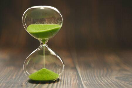 Reloj de arena con arena que cae dentro de una bombilla de vidrio, pasando el tiempo o tiempo perdido sobre un fondo de madera con espacio para texto