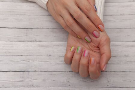 Multicolored modern manicure, nail design. Summer mood, on wooden background.