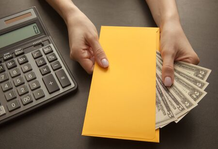 Business and profit concept with calculator, money in a yellow envelope in female hands, close-up