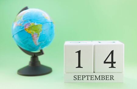 Calendar made of wood on a light green background, 14 day of the month September, autumn 14th day Imagens