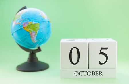 Calendar made of wood on a light green background, 05 day of the month October, autumn 5th day Imagens