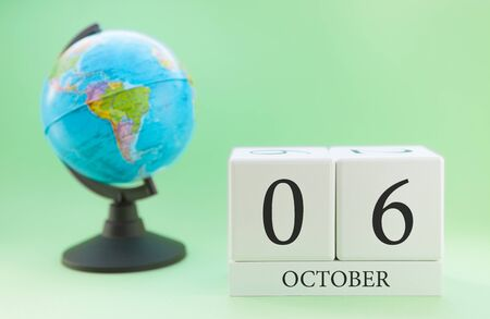 Calendar made of wood on a light green background, 06 day of the month October, autumn 6th day Imagens