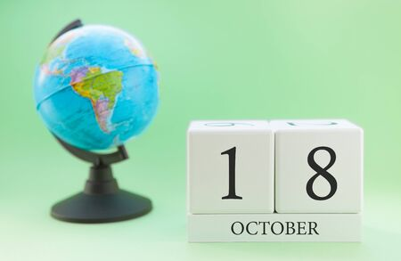 Calendar made of wood on a light green background, 18 day of the month October, autumn 18th day