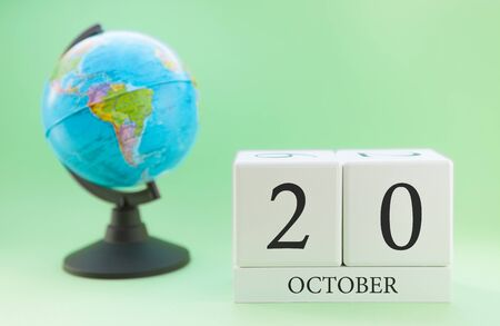 Calendar made of wood on a light green background, 20 day of the month October, autumn 20th day Banco de Imagens