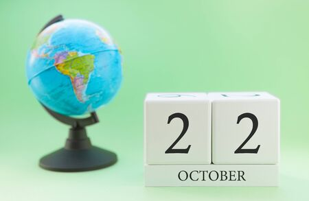 Calendar made of wood on a light green background, 22 day of the month October, autumn 22nd day