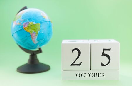Calendar made of wood on a light green background, 25 day of the month October, autumn 25th day