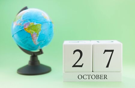 Calendar made of wood on a light green background, 27 day of the month October, autumn 27th day