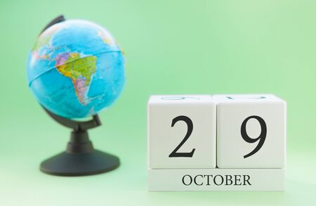 Calendar made of wood on a light green background, 29 day of the month October, autumn 29th day