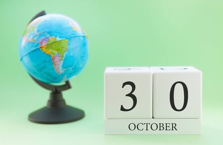 Calendar made of wood on a light green background, 30 day of the month October, autumn 30th day