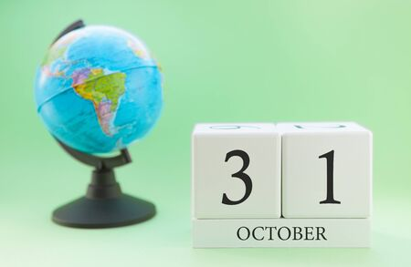 Calendar made of wood on a light green background, 31 day of the month October, autumn 31st day