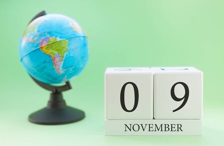 Planner wooden cube with numbers, 9 day of the month of November, autumn