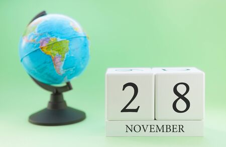 Planner wooden cube with numbers, 28 day of the month of November, autumn