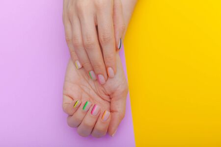 Stylish trendy female manicure. Beautiful young womans hands on violet and yellow background. Top view