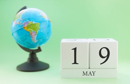Planner wooden cube with numbers, 19 day of the month of May, spring Foto de archivo